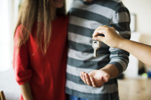 Picture of person handing over keys.