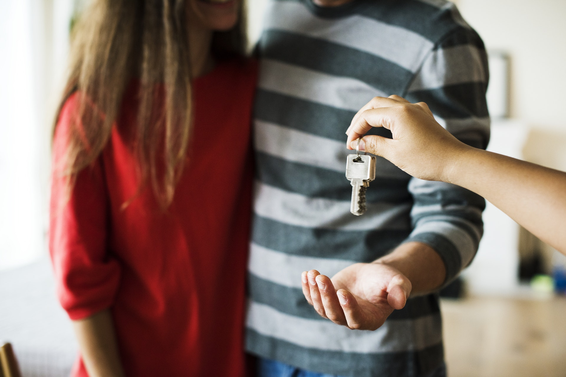 Decorative image of person handing over keys.